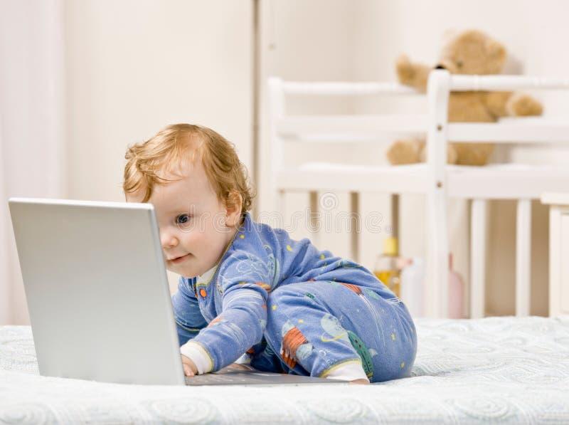 De jongen van de peuter het typen op laptop in slaapkamer stock afbeeldingen