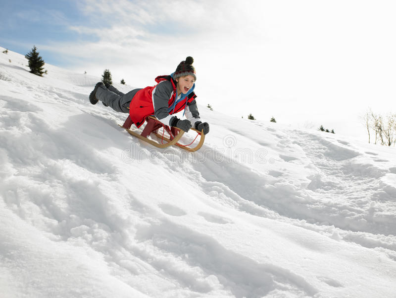 De Jongen van de pre-tiener op een Slee in de Sneeuw stock foto's