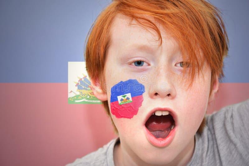 De jongen van de roodharigeventilator met haitian vlag schilderde op zijn gezicht stock fotografie