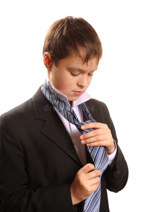 De jongen van de tiener bindt een band op een witte achtergrond stock afbeeldingen
