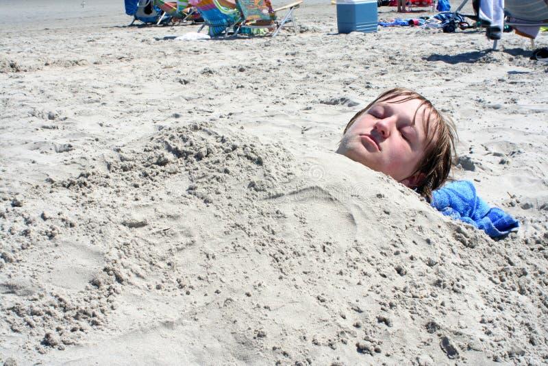 De Jongen van de tiener die in Zand wordt begraven stock foto