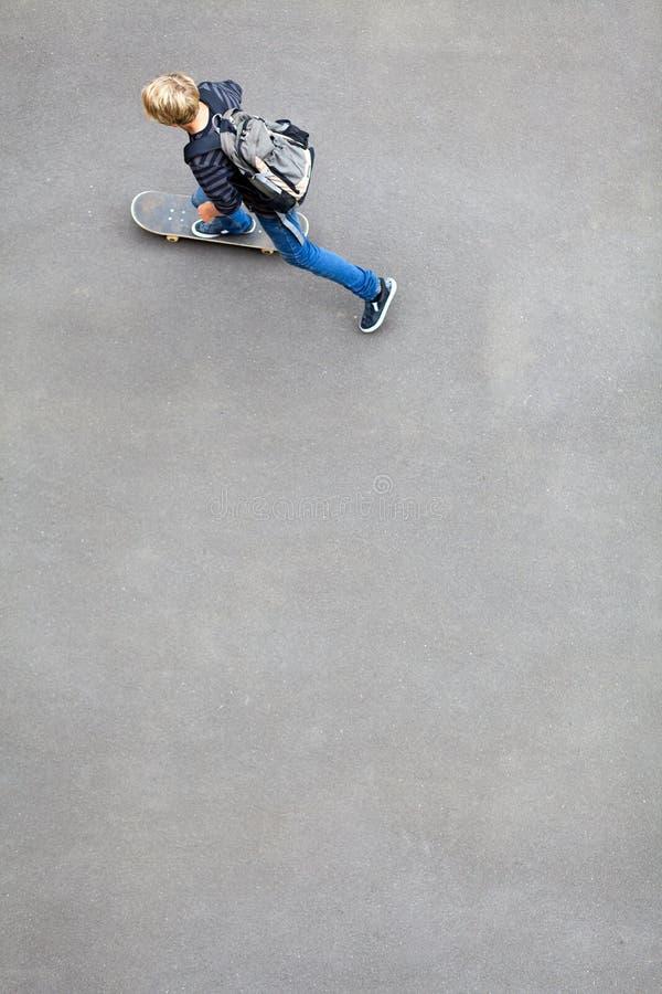 De jongen van de tiener het met een skateboard rijden stock fotografie
