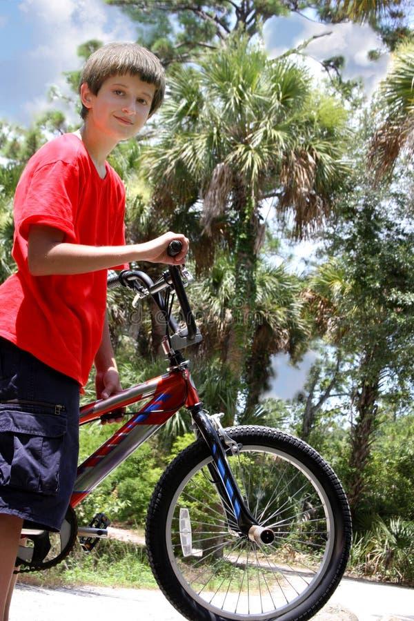 De jongen van de tiener met fietsen stock foto