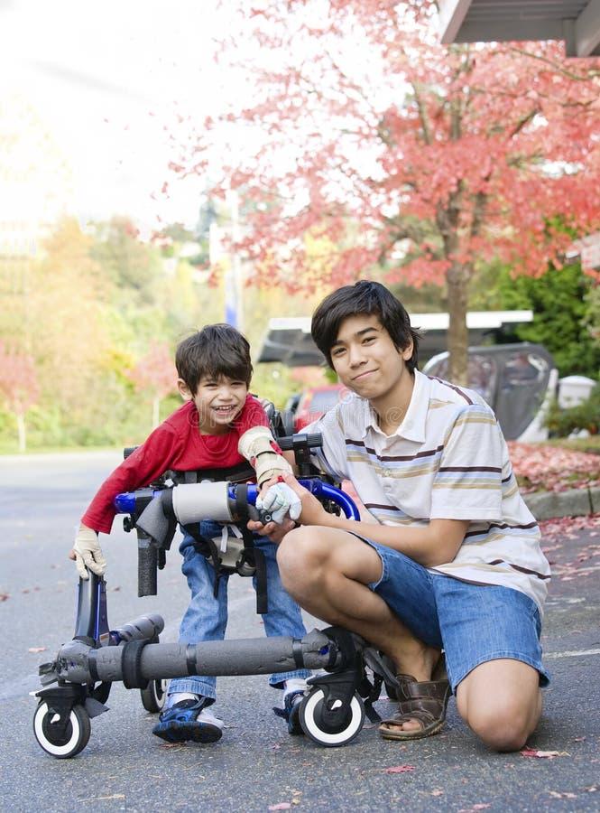 De Jongen Van De Tiener Met Gehandicapt Weinig Broer In Leurder Royalty-vrije Stock Fotografie