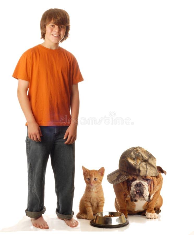 De jongen van de tiener met huisdierenhond en kat stock afbeelding
