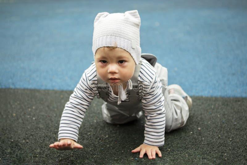 De jongen van het babymeisje in grijs kruipt op de speelplaats Kind op alle fours royalty-vrije stock afbeelding