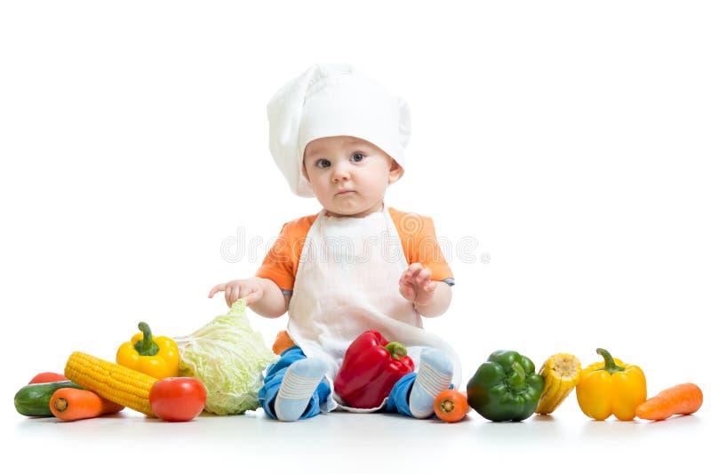 De jongen van het chef-kokkind met groenten die op witte achtergrond wordt geïsoleerd stock foto