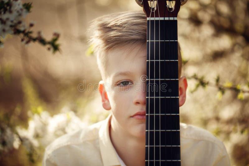 De jongen van het close-upportret met gitaar in de zomerdag stock afbeeldingen