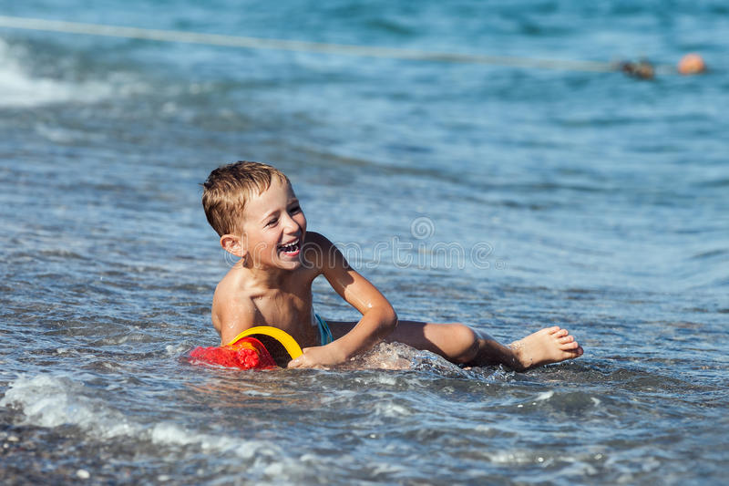 De jongen van het kind op overzees strand stock fotografie