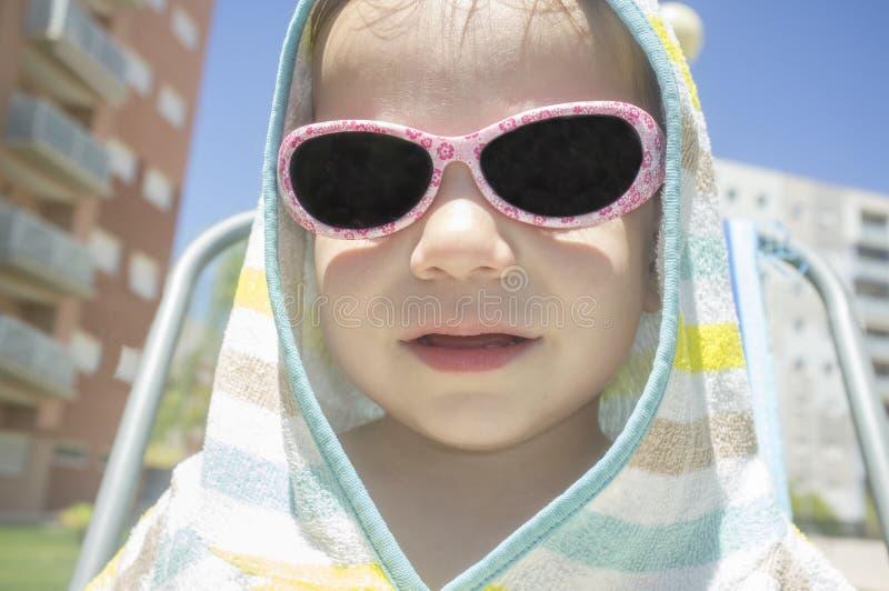 de jongen van de 2 jaarbaby met ponchohanddoek met een kap na het zwemmen royalty-vrije stock afbeelding