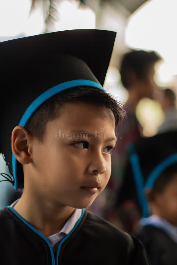De jongen van kleuterschool een diploma die wordt behaald die stock afbeelding