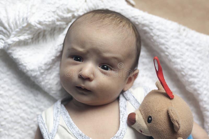 de jongen van de 2 maandbaby het liggen Close-up van aanbiddelijke leuke pasgeboren babyjongen van twee maanden Baby met verdacht stock afbeelding