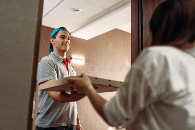 De jongen van de pizzalevering geeft doos aan vrouwelijke klant stock foto