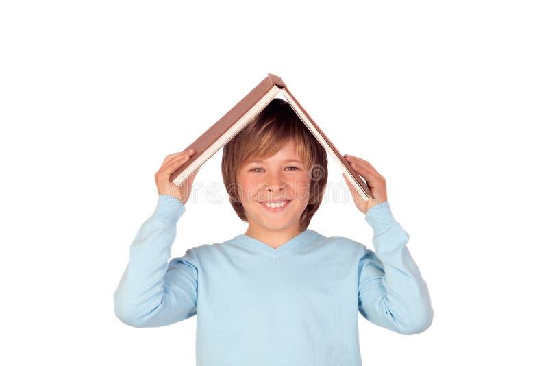 De jongen van Preteen met een groot boek oh zijn hoofd stock foto's