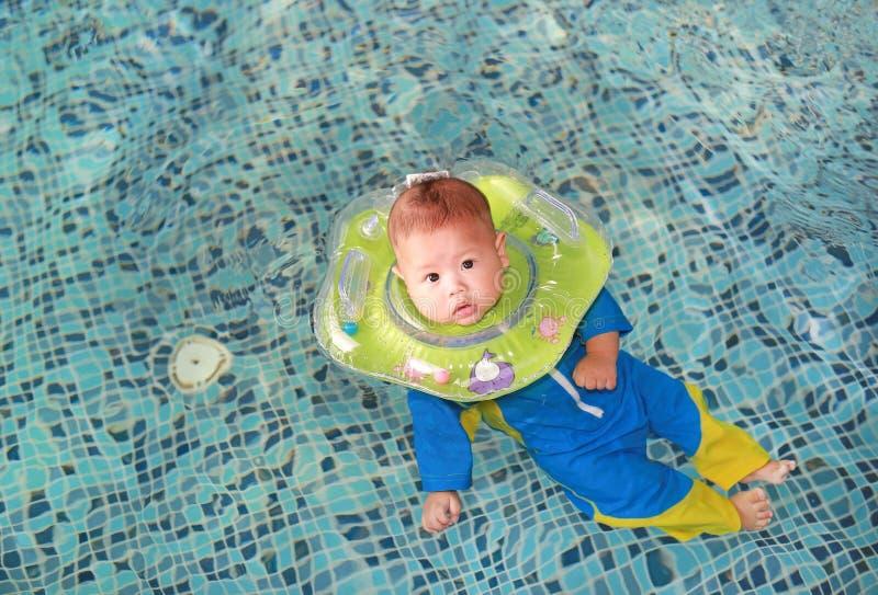 De jongen van de zuigelingsbaby de opleiding om in pool met veiligheid door babyhals te zwemmen drijft stock foto's