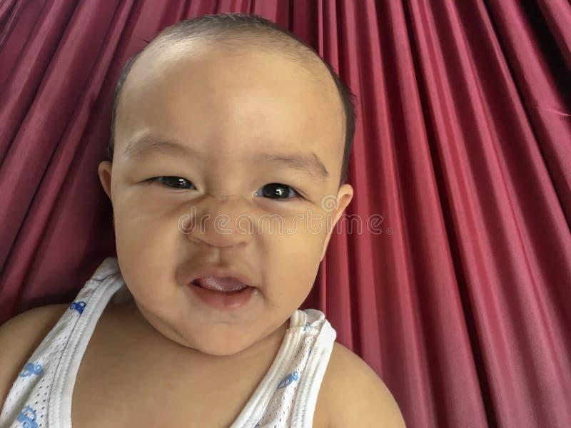 De jongen van de de Zuigelingsbaby van Thailand Azië ligt en lacht stock foto
