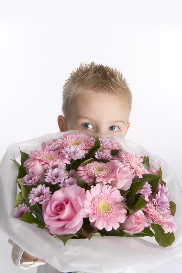 De jongen verbergt achter een boeket van bloemen stock fotografie