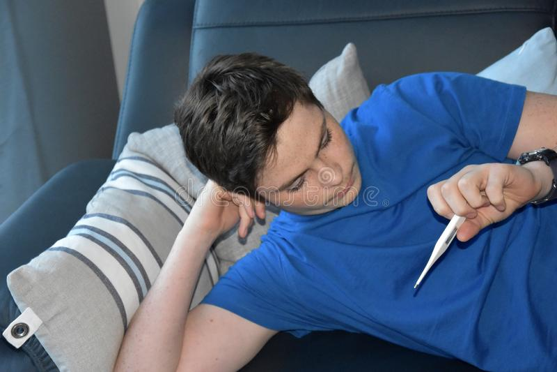 De jongen vergt zijn temperatuur met een koortsthermometer stock afbeeldingen