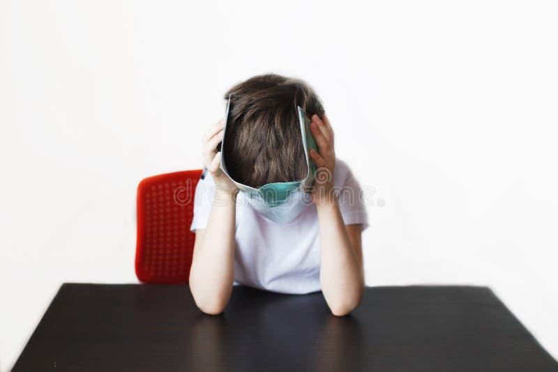De jongen is vermoeid van het doen van thuiswerk stock afbeelding
