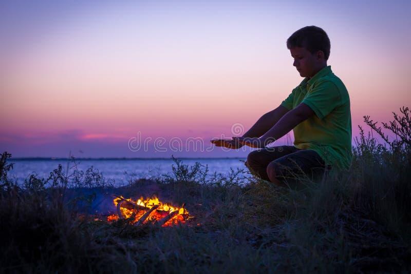De jongen verwarmt door het kampvuur op het strand bij zonsondergang stock foto's