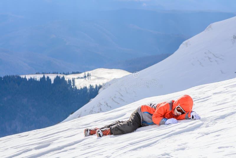 De jongen viel onderaan over verse sneeuw Gelukkige jongen die op sneeuw leggen Leuke Li stock fotografie
