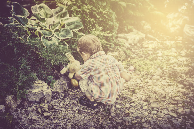 De jongen vindt een stuk speelgoed van Pasen Bunny Rabbit in een Retro Tuin - stock afbeeldingen