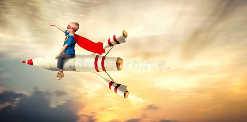 De jongen in de vlieg van het superherokostuum op een raket en toont super capaciteiten stock foto's