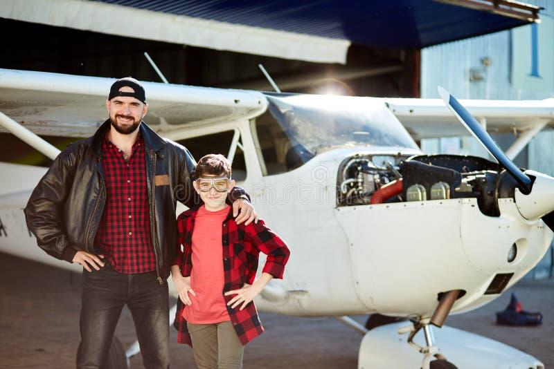 De jongen in vliegeniersglazen voelt blij zijn vader nam hem aan hangaar waar hij de reparatiewerken maakt stock fotografie