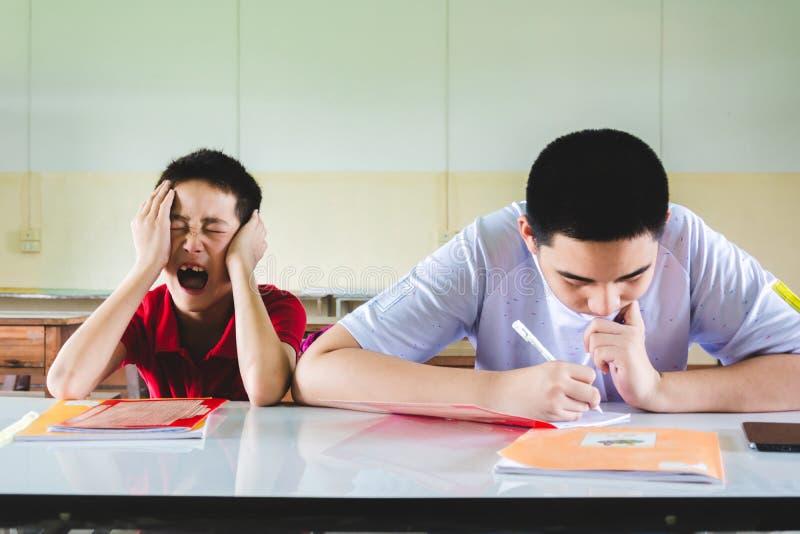 De jongen voelt in slaap in het klaslokaal maar een andere ??n doend thuiswerk stock foto's