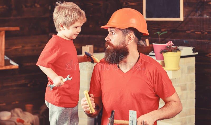 De jongen, vrolijk kind houdt moersleutelmoersleutel, lerend gebruikshulpmiddelen met papa Vader, ouder met baard in beschermende royalty-vrije stock foto