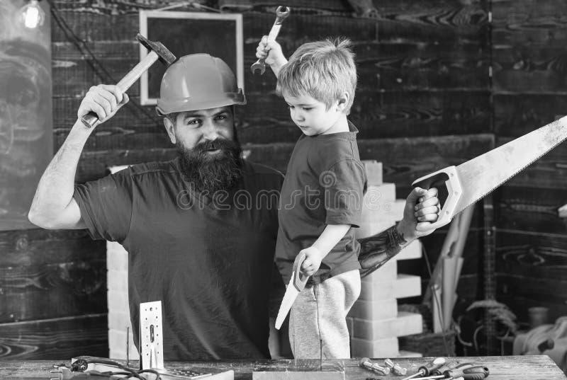 De jongen, vrolijk kind houdt stuk speelgoed zaag, die pret hebben terwijl het handcrafting met papa Vader, ouder met baard in be stock afbeelding