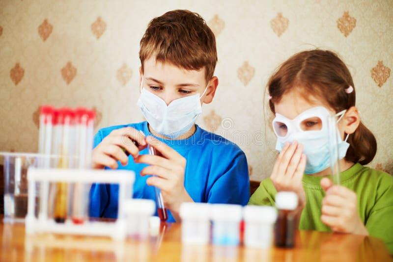 De jongen vult chemische reageerbuis met specimen en het meisje zit dichtbij royalty-vrije stock afbeelding