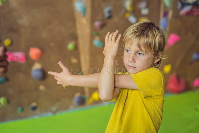 De jongen warmt alvorens een rotsmuur te beklimmen binnen op royalty-vrije stock foto