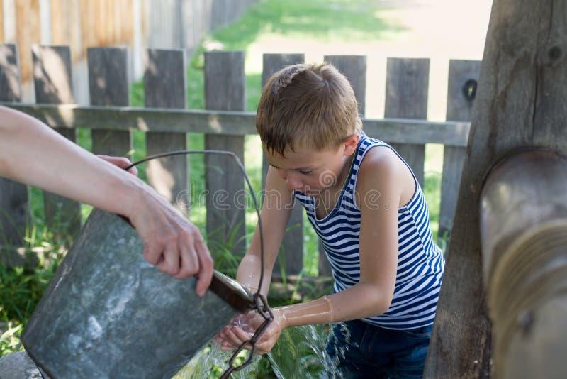 De jongen wast bronwater. stock afbeeldingen