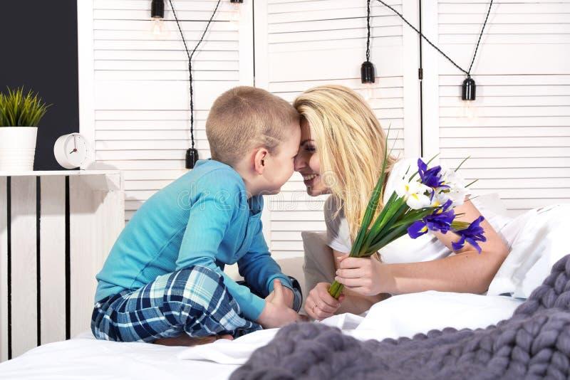 De jongen wekt mamma en geeft haar een boeket van bloemen in bed Het vieren de Dag van de Vrouw De dag van de moeder `s royalty-vrije stock afbeeldingen