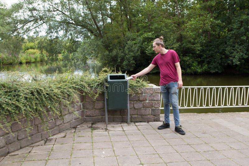 De jongen werpt huisvuil in het afval stock foto's