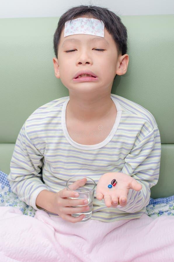 De jongen wil geen geneeskunde eten stock fotografie