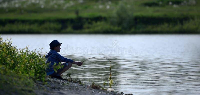 De jongen zit door de rivier en wil vissen stock fotografie