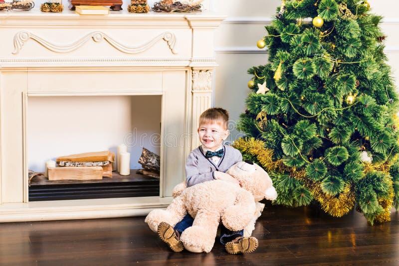 De jongen zit met teddybeer op de achtergrond van de Kerstboom stock afbeelding