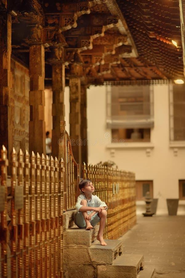 De jongen zit op de portiek stock foto