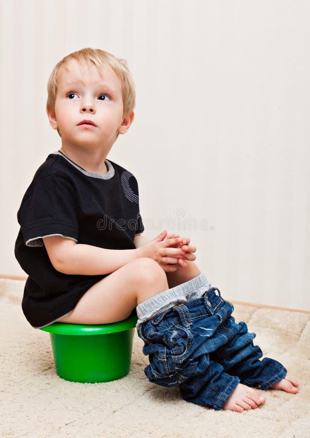 De jongen zit op de pot royalty-vrije stock afbeelding