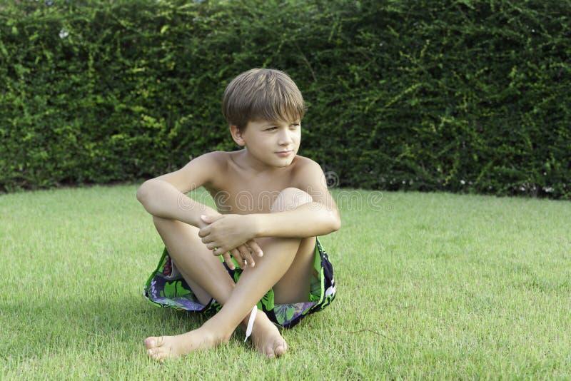 De jongen zit op een gazon stock foto's