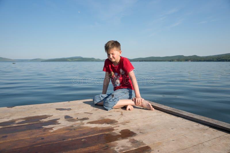 De jongen zit op een houten pijler en maakt een gefrustreerd grimas tegen het meer op een zonnige dag royalty-vrije stock afbeelding