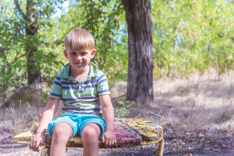 De jongen zit op een oude bank, in een verlaten park en kijkt rond met een droevig gezicht stock afbeelding