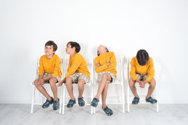 De jongen zit op een stoel en wacht op zijn draai Hij is v stock afbeeldingen