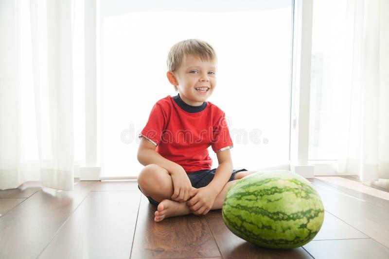De jongen zit op de vloer Naast het is een watermeloen royalty-vrije stock afbeeldingen