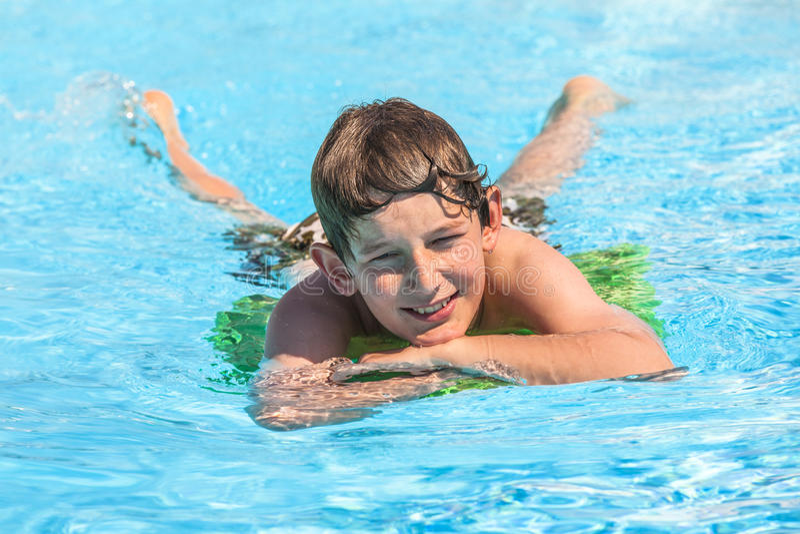 De jongen zwemt in een pool tijdens vakantie stock afbeeldingen