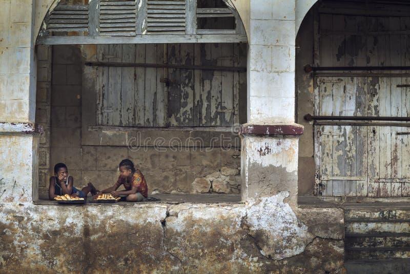 De jongens die van Madagascar brood op een geruïneerd gebouw eten royalty-vrije stock foto's