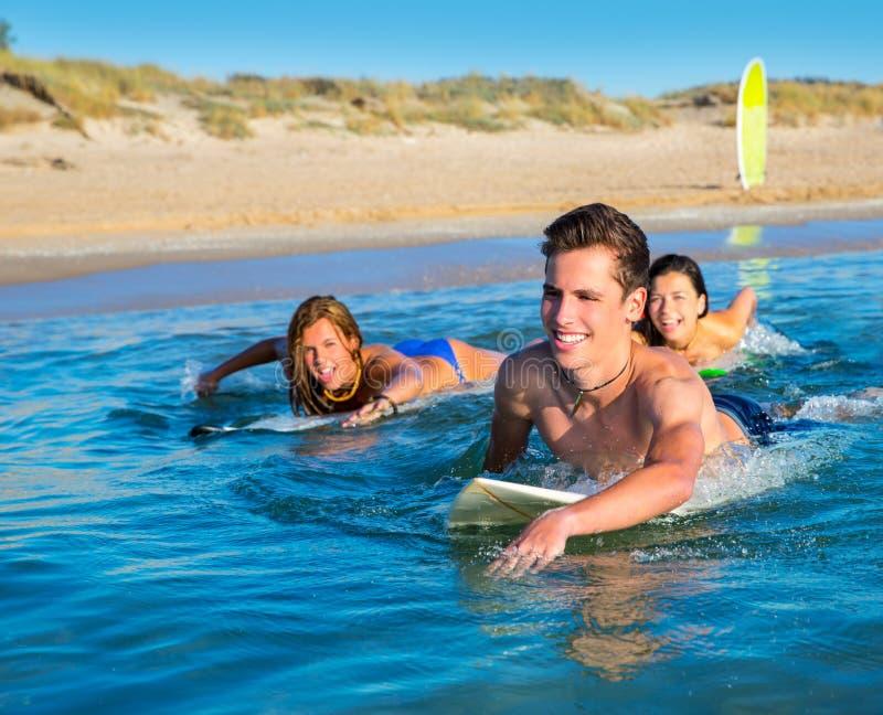 De jongens en de meisjes die van de tienersurfer ove surfplank zwemmen royalty-vrije stock afbeeldingen