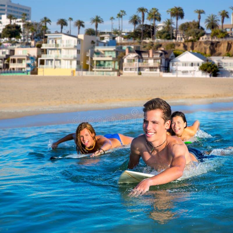 De jongens en de meisjes die van de tienersurfer ove surfplank zwemmen royalty-vrije stock foto's
